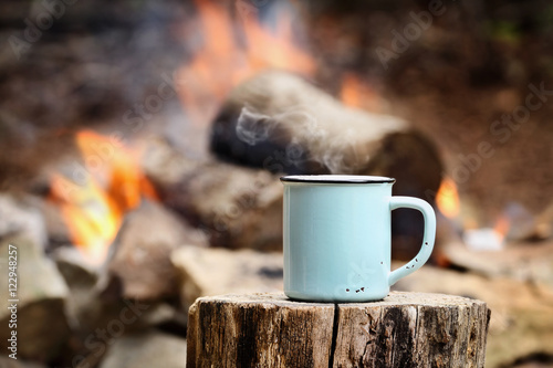Fotobehang Kamperen Blue enamel cup of hot steaming coffee sitting on an old log by an outdoor campfire. Extreme shallow depth of field with selective focus on mug.