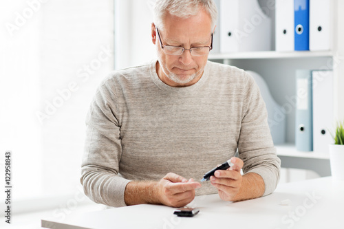 Fotomural  senior man with glucometer checking blood sugar