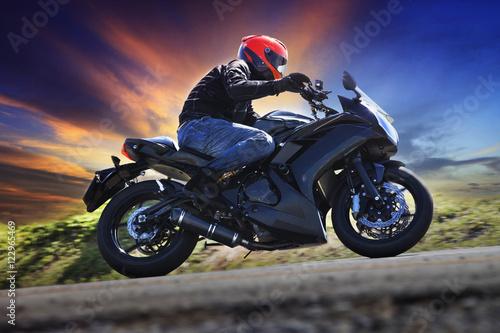 mlody-mezczyzna-jadacy-motocyklem-na-asfaltowej-drodze-wieczorowa-pora