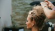 Hairdresser makes hairstyle young woman.Hairdresser in a beauty salon doing hair young woman.