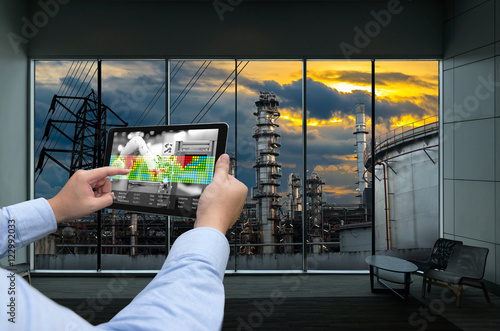 Industry 4.0 concept .Man hand holding tablet with Augmented reality screen and automate wireless Robot arm software at industrial room in smart factory.Window showing oil refinery industry background