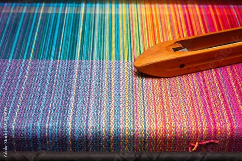 Fotografiet  Weaving shuttle on the color warp