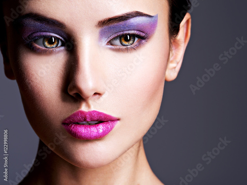 Poster Beauty Beautiful girl's face closeup with purple eye make-up. fashion m
