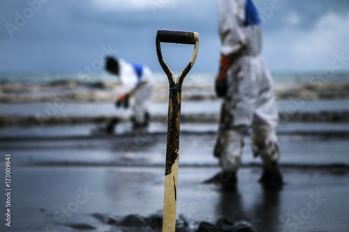 Fotografia  Workers remove crude oil from a beach