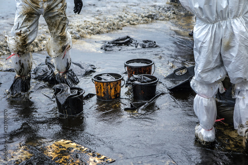 Fotografija  Workers remove crude oil from a beach