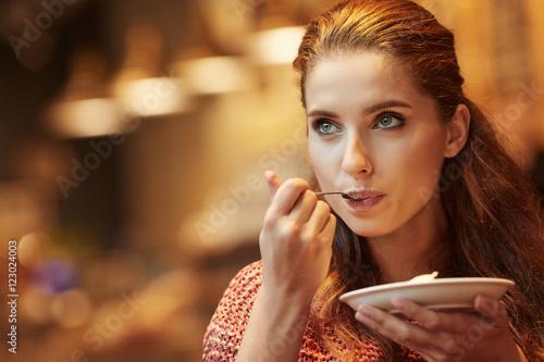Fototapeta young beautiful woman eating a dessert obraz
