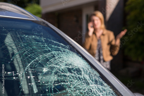 Fototapeta Woman Phoning For Help After Car Windshield Has Broken obraz