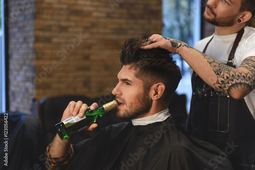 guy getting haircut while drinking