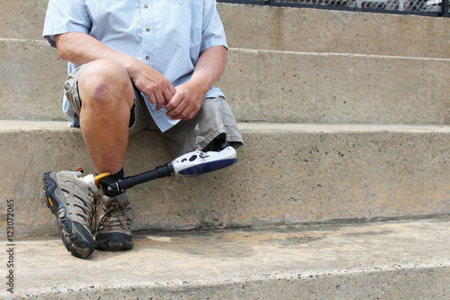 Photo Amputee with legs crossed sitting on concrete bleachers