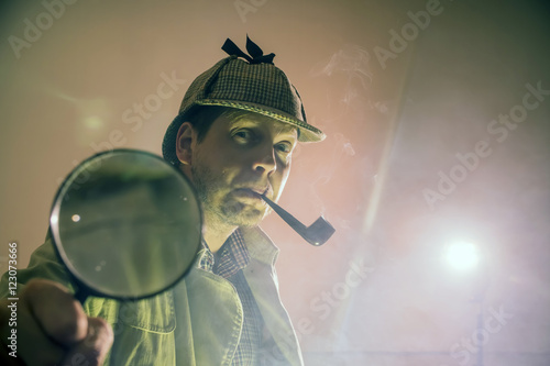 Valokuva  sherlock holmes in studio etective at work with magnifying glass and pipe