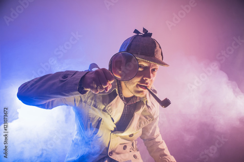 sherlock holmes in studio etective at work with magnifying glass and pipe Canvas Print