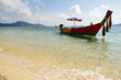 Traditional beautiful wooden boat in Thailand anchored near the beach.