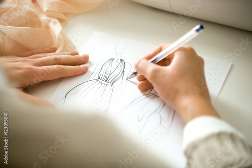 Hands drawing a black ink clothing design sketch, view over the shoulder, closeu Wallpaper Mural