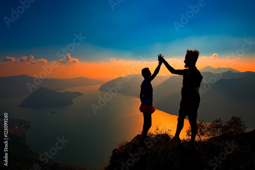 Fototapety, obrazy: A pair shake hands in victory on top of a mountain