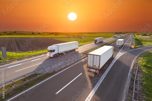 Fototapeta Dostawa transportu ciężarówki na autostradzie o zachodzie słońca