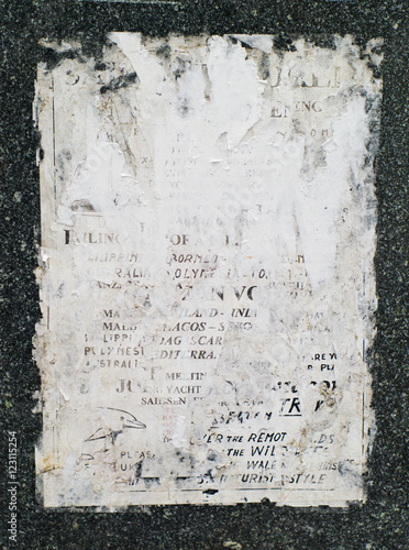 closeup shot of old, faded, and torn posters on granite wall © rockyoubaby
