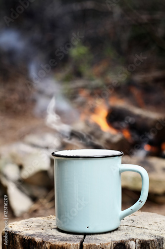 Poster Camping Blue enamel cup of hot steaming coffee sitting on an old log by an outdoor campfire. Extreme shallow depth of field with selective focus on mug.