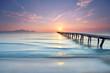 Sonnenaufgang über dem alten Holzsteg am Strand