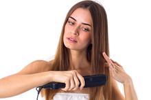 Woman Using Hair Straightener