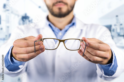 Fotografía  eyesight care concept - optician giving new optical glasses