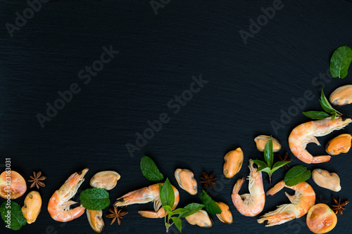 Poster Coquillage Preparing fresh seafood in the kitchen with gourmet pink shrimp and mussels surrounded by fresh herbs and spices on black stone background