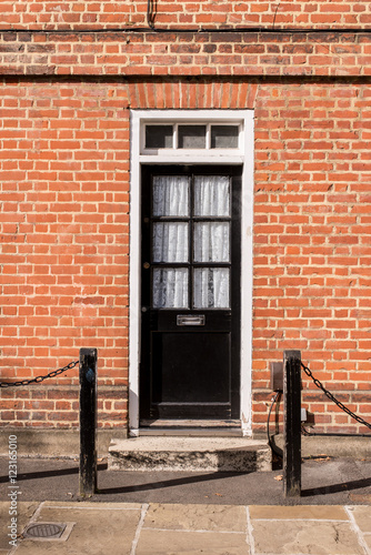 Victorian Black External Wooden Door With Glass Panels On A Red