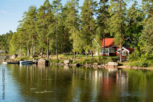 Traditional, red wooden house on a lake in Småland, Sweden, in an early summer morning