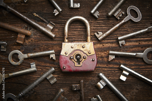 Photographie  Vintage rusty padlock surrounded by old keys on a weathered steel background