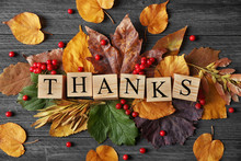Autumn Composition Of Leaves, Berries And Cubes With Word THANKS On Wooden Background. Thanksgiving Day Concept