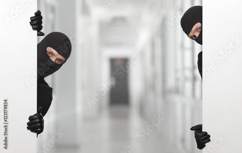 Fototapeta Criminal concept - robber hiding behind a empty white sign