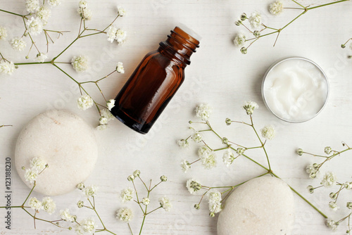 Fotografia  Bottle of essential oil, body care cream sample, stones, flowers