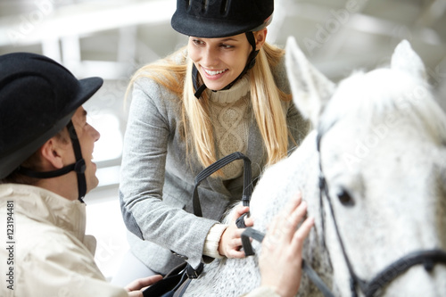 Foto auf AluDibond Reiten Portrait of happy woman with sports helmet sitting on the horse and looking at her husband