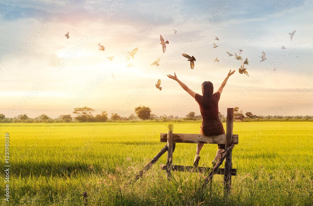 Fototapety, obrazy: Woman praying and free bird enjoying nature on sunset background