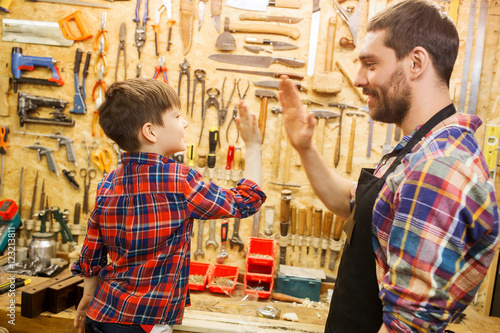 Obraz father and little son making high five at workshop - fototapety do salonu