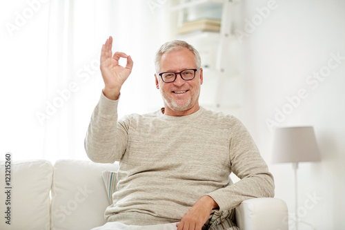 Valokuva  smiling senior man showing ok hand sign at home