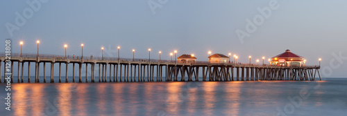 Panorama of Huntington beach pier lit up by street lights at dusk