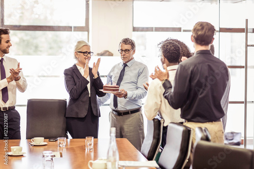 Senior man presenting cake with candles to business team in boardroom