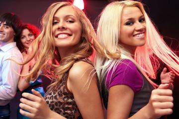 Dwie młode blondynki tańczą z przyjaciółmi
