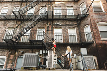 Women Climbing Fire Escape Lad...
