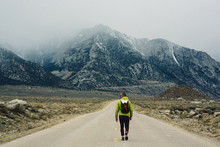 Rear View Of Hiker On Road By Mountains, Lone Pine, California, USA