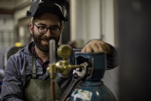 Welder Looking At Gas Canister Smiling