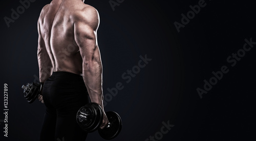 Bodybuilder doing exercises with dumbbells