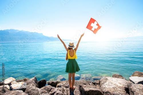Carta da parati Young female traveler with swiss flag enjoying great view on Geneva lake in Swit