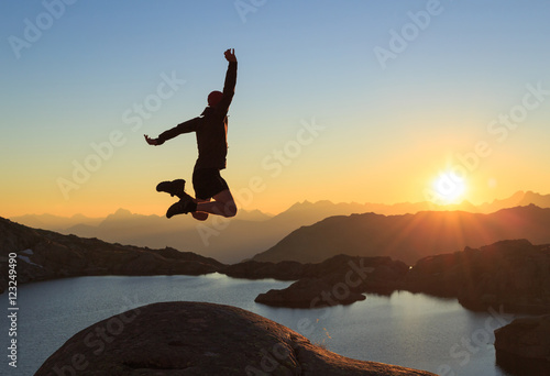Photo Hiker jumping out of happiness during a clear sunset at a lake near Chamonix