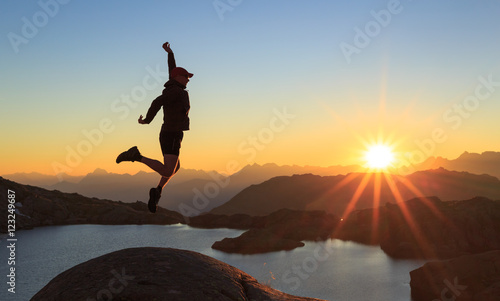 Photo Man jumping out of joy during a clear sunset at a lake near Chamonix