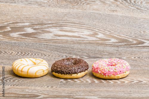 Photo  fresh colorful donuts, isolated on a wooden background