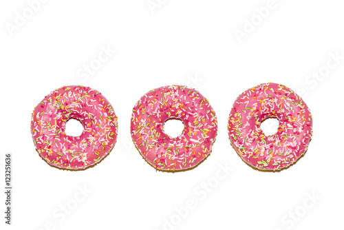 Three  glazed strawberry donuts on white background, top view Canvas Print