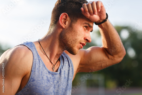 Portrait of fatigued fitness guy on hot sunny day Canvas Print