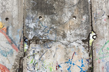 Close-up Part Of Berlin Wall. View From The West Berlin Side Of Graffiti Art On The Wall