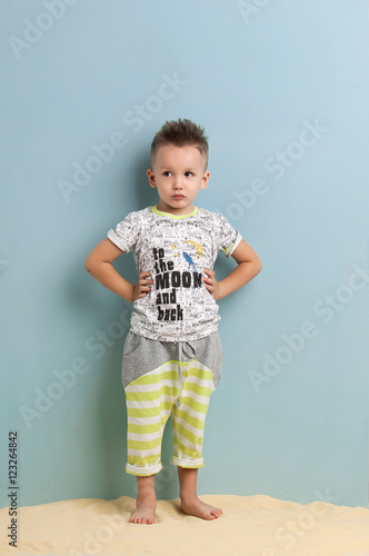 3ff6440a4 little boy in shorts and t-shirt standing on the sand on a light blue  background